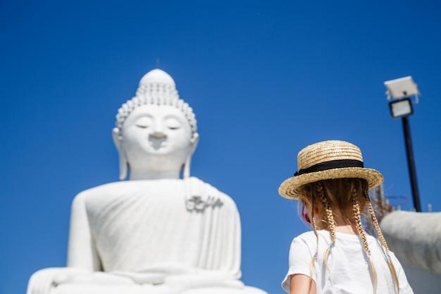 Hintere ansicht des kleinen mädchens stehende nahe großer buddha-statue in phuket, thailand.