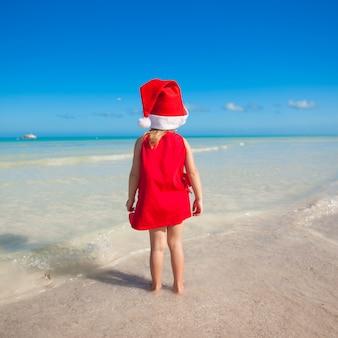 Hintere ansicht des kleinen netten mädchens im roten hut weihnachtsmann auf dem strand