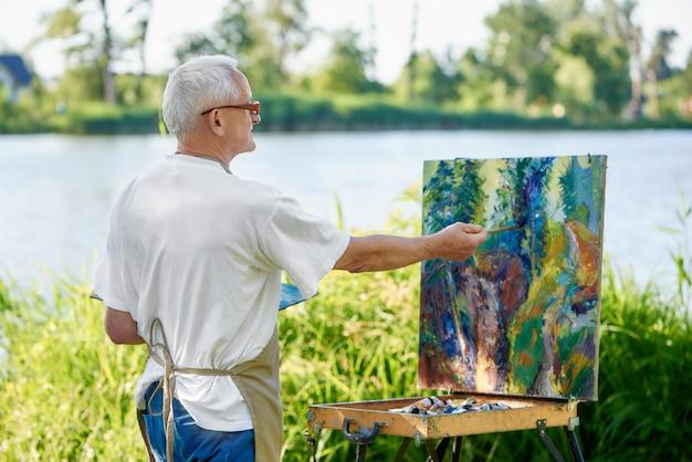 Hintere ansicht des kreativen malers malt bunte abstrakte malerei auf freilicht.