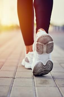 Hintere ansicht des läufers in den sportturnschuhen, die draußen laufen