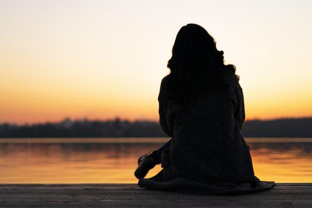 Hintere ansicht des langen haar brunettemädchens, das auf dem pier nahe see zur sonnenuntergangzeit sitzt.