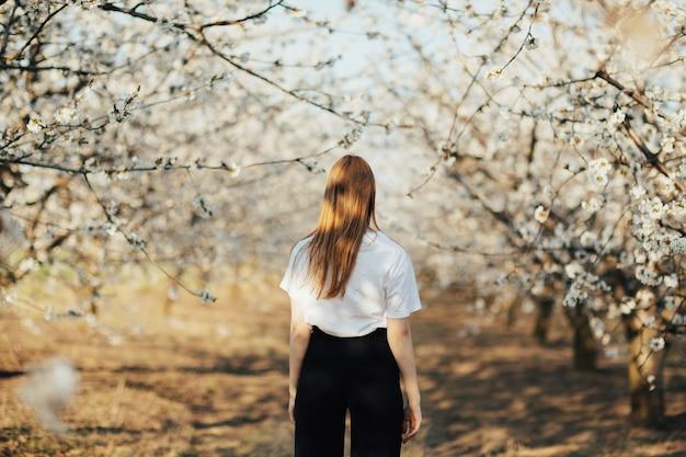 Hintere ansicht des mädchens, das unter blühenden bäumen im garten auf hügel am sonnigen frühlingstag geht.
