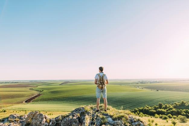Hintere ansicht des männlichen wanderers mit dem rucksack, der grüne rollenlandschaft betrachtet
