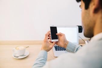 Hintere Ansicht des Mannes arbeitend mit Smartphone