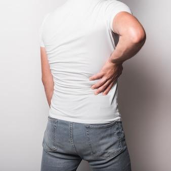 Hintere ansicht des mannes, der rückenschmerzen gegen weißen hintergrund hat