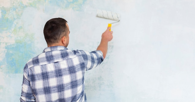 Hintere ansicht des mannes eine wand malend