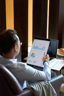 Hintere ansicht des mannes gesetzt im lehnsessel im café diagramme und diagramme vor darstellung analysierend