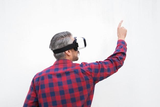 Hintere ansicht des mannes in vr-kopfhörer zeigend mit dem finger