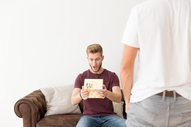Hintere ansicht des mannes mit dem überraschten mann, der auf sofa mit dem halten der geschenkbox sitzt