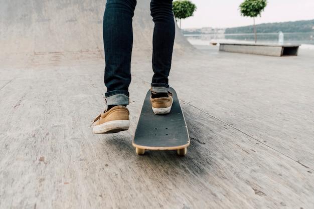Hintere ansicht des mannes skateboard fahrend