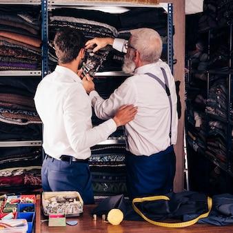 Hintere ansicht des mannes und des älteren männlichen schneiders, die gewebe vom regal in seinem shop wählen