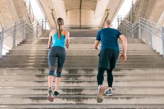 Hintere Ansicht des männlichen und weiblichen Athleten, der auf dem Treppenhaus rüttelt