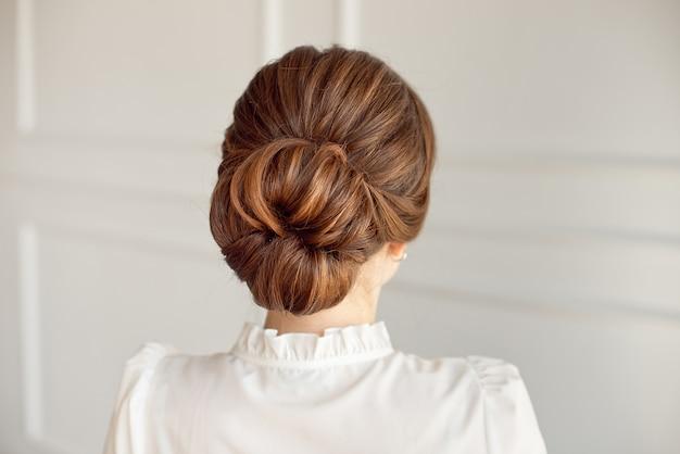 Hintere ansicht des mittleren brötchens der weiblichen frisur mit dem dunklen haar