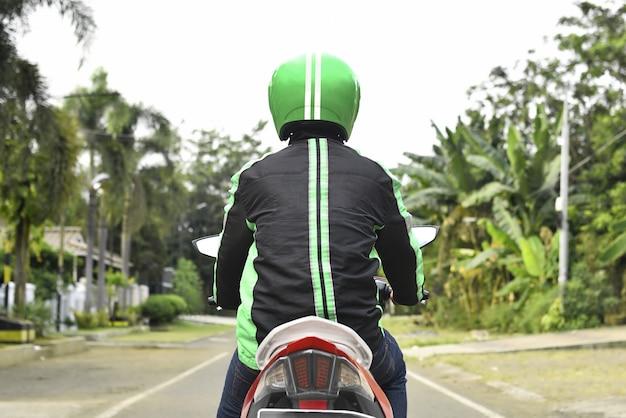 Hintere ansicht des motorradtaxis passagier suchend