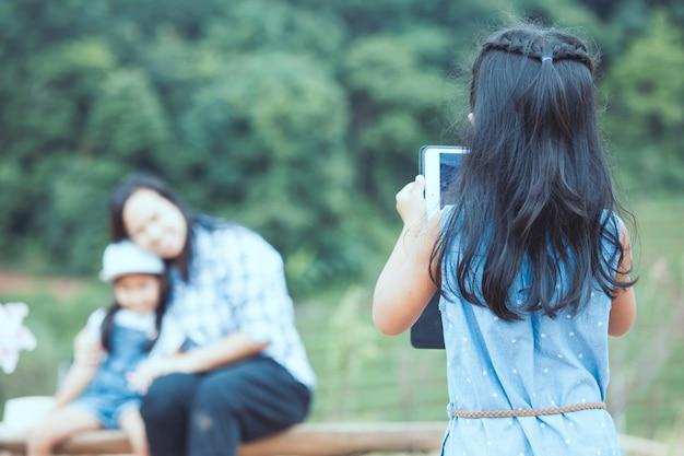 Hintere ansicht des netten asiatischen kindermädchens benutzt die tablette, die ein foto ihre familie im park macht