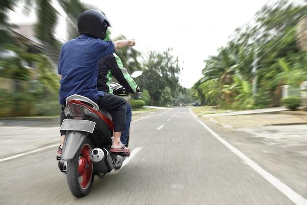 Hintere ansicht des passagiers den weg zum motorradtaxifahrer weisend