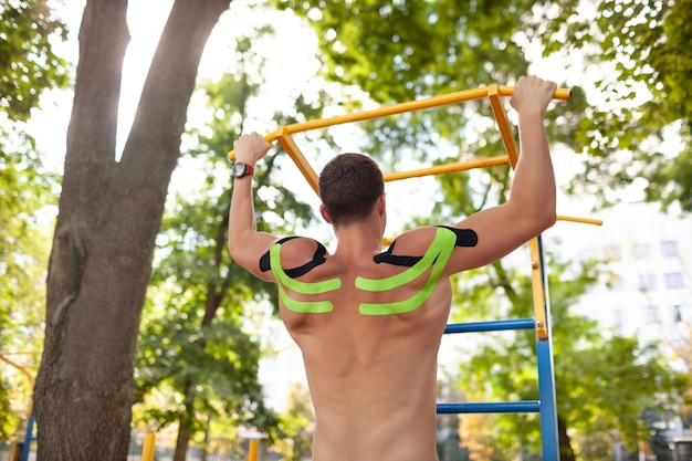 Hintere ansicht des professionellen männlichen athleten mit buntem kinesiologischem taping auf dem rücken