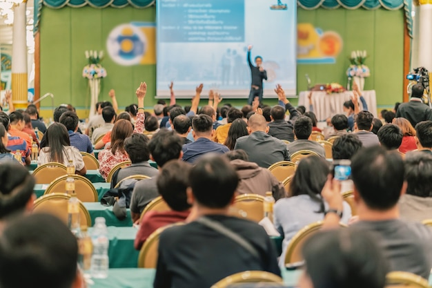 Hintere ansicht des publikums hand zeigend, um die frage vom sprecher auf dem stadium zu beantworten