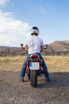 Hintere ansicht des radfahrers im sturzhelm, der auf motorrad in einem berggebiet sitzt.