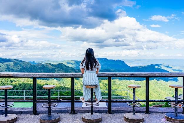 Hintere ansicht des reisenden der jungen frau, der die ansicht an pino late-kaffeestube in khao kho phetchabun, thailand sitzt und genießt