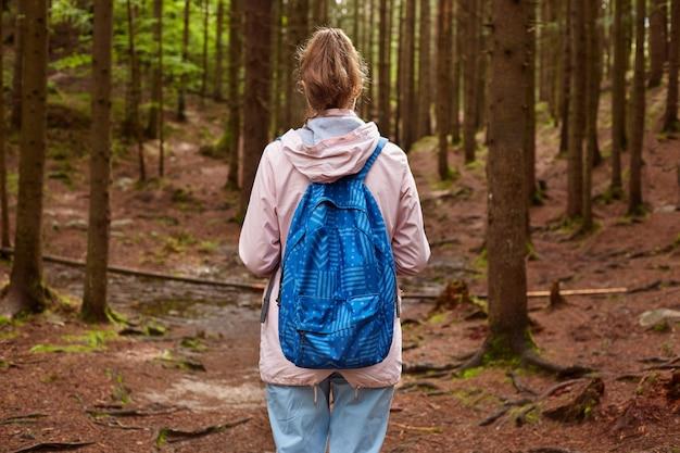 Hintere ansicht des schlanken athletischen touristischen wanderermädchens mit blauem rucksack, der durch bergkiefernwald geht. frau, die zeit im freien verbringt