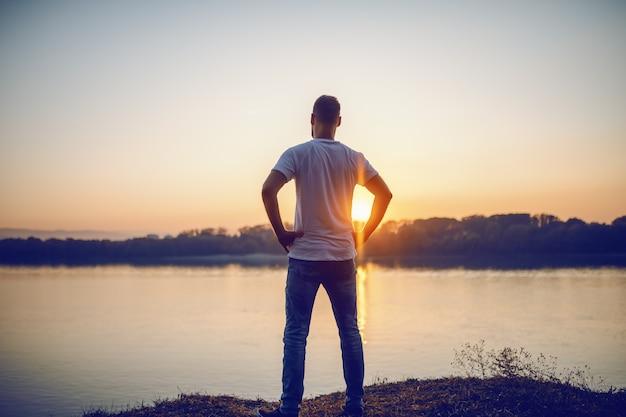 Hintere ansicht des schönen kaukasischen mannes, der mit den händen auf den hüften auf der klippe steht und fluss und schönen sonnenuntergang betrachtet.