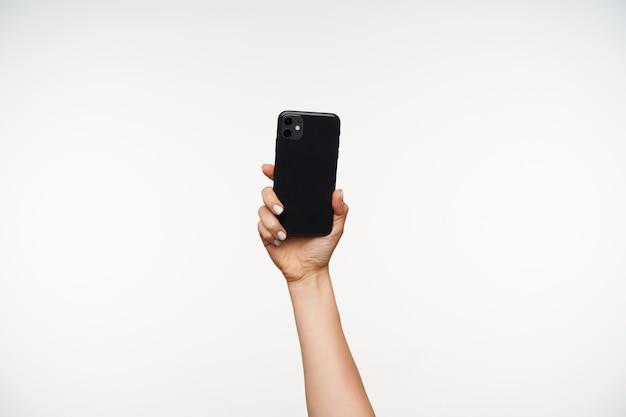 Hintere ansicht des schwarzen modernen mobiltelefons, das von der jungen frau mit weißer maniküre gehalten wird, lokalisiert auf weiß. menschliche hände und gestik