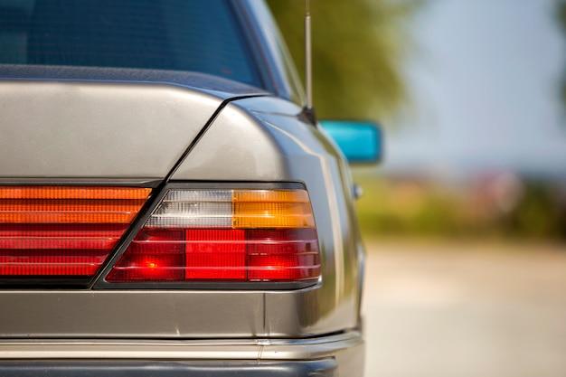 Hintere ansicht des silbernen autos parkte auf gepflasterter straße in der ruhigen gegend auf sonnigem hellem hintergrund. transport- und stadtparkkonzept.