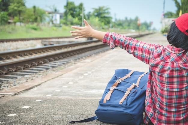 Hintere ansicht des sitzens des tourismus der jungen frau (passagier) und zeigen ihre hand auf plattform an der bahnstation. warten auf den transport