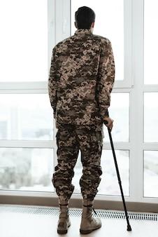 Hintere ansicht des soldaten lehnend auf krücke durch fenster.