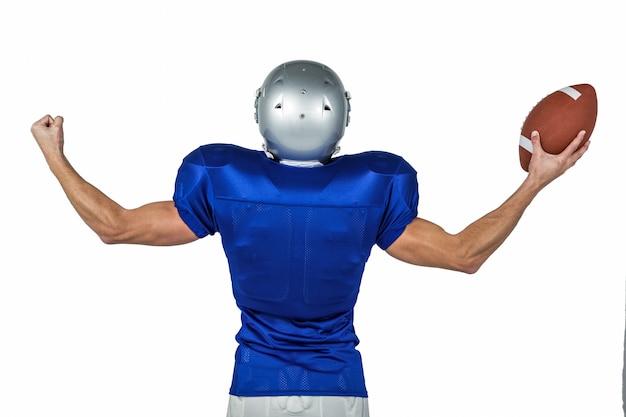 Hintere ansicht des spielers des amerikanischen fußballs, der muskeln beim halten des balls gegen weißen hintergrund biegt