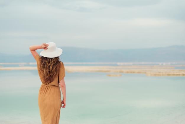 Hintere ansicht des tragenden kleides des stilvollen mädchens auf küste