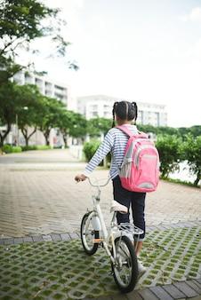 Hintere ansicht des tragenden rucksacks des weiblichen schülers und des ziehens des fahrrades in der straße