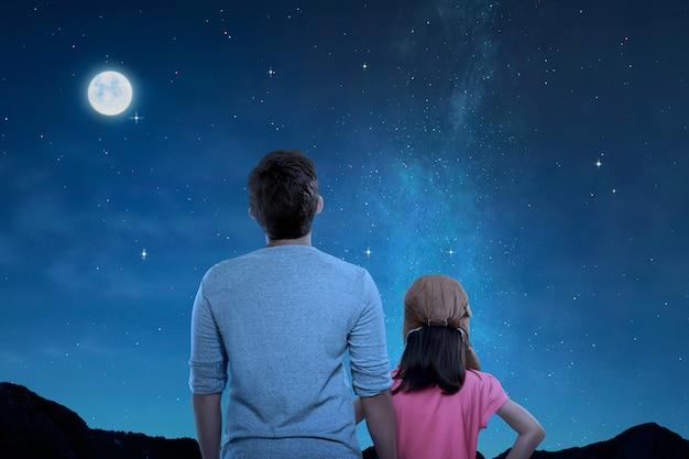 Hintere ansicht des vaters und der kleinen tochter, die nachtszene betrachten