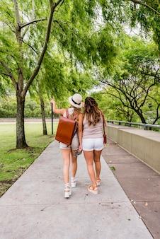 Hintere ansicht des weiblichen touristen zwei, der in den garten geht