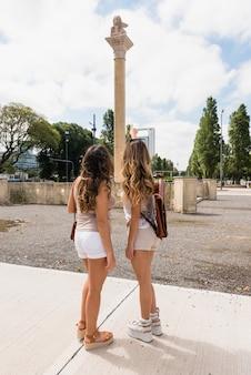 Hintere ansicht des weiblichen touristen zwei, der säule in der stadt betrachtet
