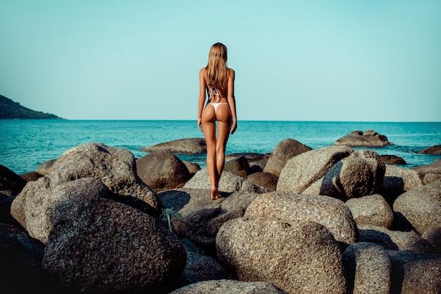 Hintere ansicht dünnes mädchen in einem bikini, der auf den felsen betrachten blauen ozean steht. phuket. thailand.