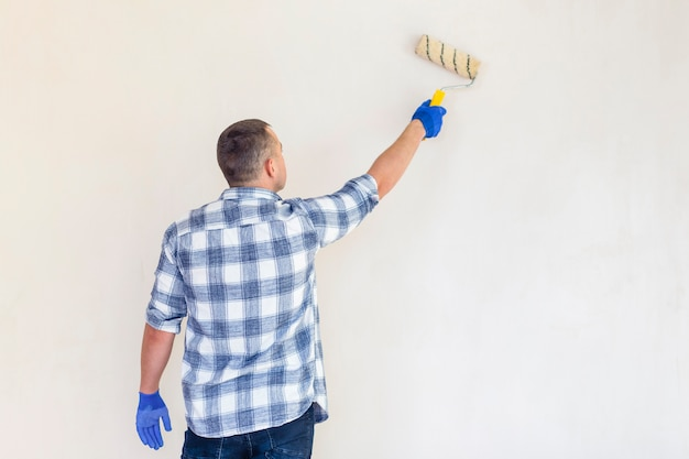 Hintere ansicht einer arbeitskraft mit farbenrollenkopienraum