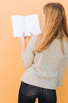 Hintere ansicht einer blonden jungen frau, die in der hand weißbuch gegen pfirsichhintergrund hält