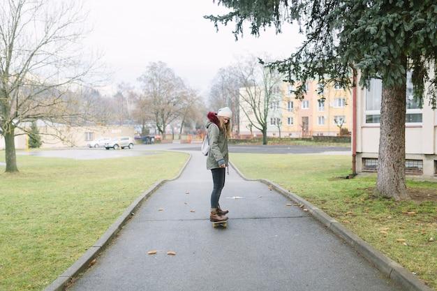Hintere ansicht einer frau, die auf skateboard fährt