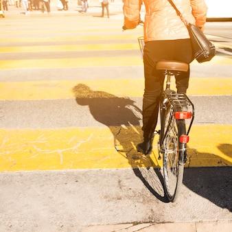 Hintere ansicht einer frau, die fahrrad auf straße fährt