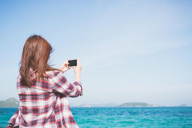 Hintere ansicht einer frau, die foto mit einer intelligenten telefonkamera am horizont auf dem strand macht.