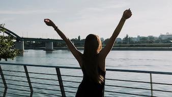 Hintere Ansicht einer Frau, die ihre Arme vor Fluss anhebt