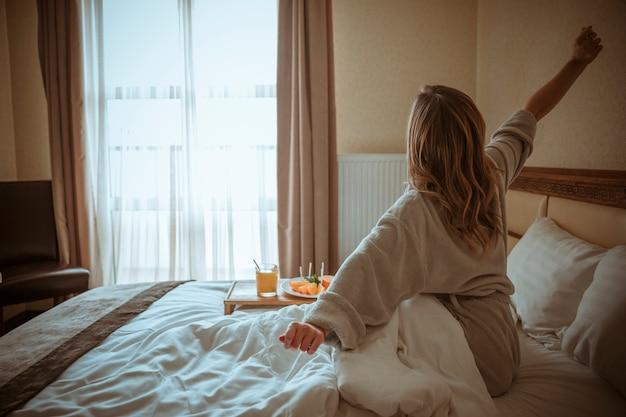 Hintere ansicht einer frau, die ihre hand nach dem aufwachen auf bett ausdehnt