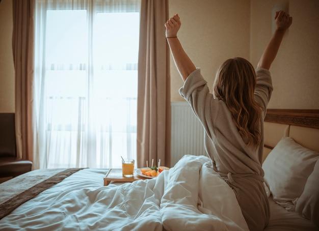 Hintere ansicht einer frau, die körper nach dem erwachen auf bett ausdehnt