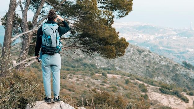 Hintere ansicht einer frau mit seinem rucksack, der auf dem felsen übersieht den bergblick steht