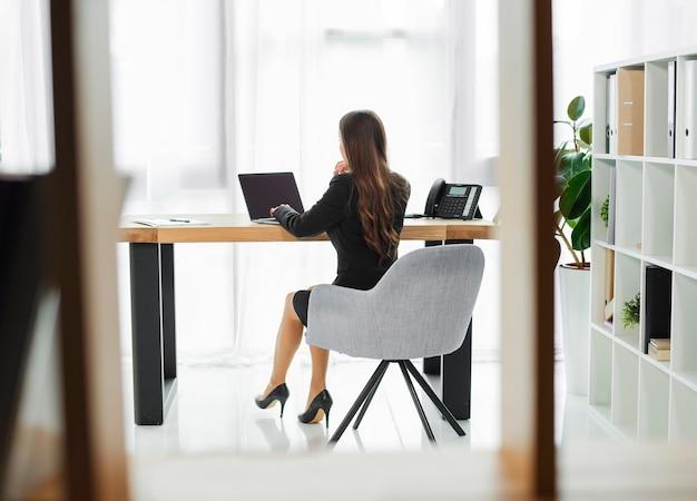 Hintere ansicht einer geschäftsfrau, die an dem laptop gesehen durch glasfenster arbeitet