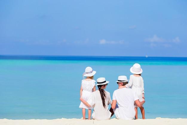 Hintere ansicht einer glücklichen familie auf tropischem strand