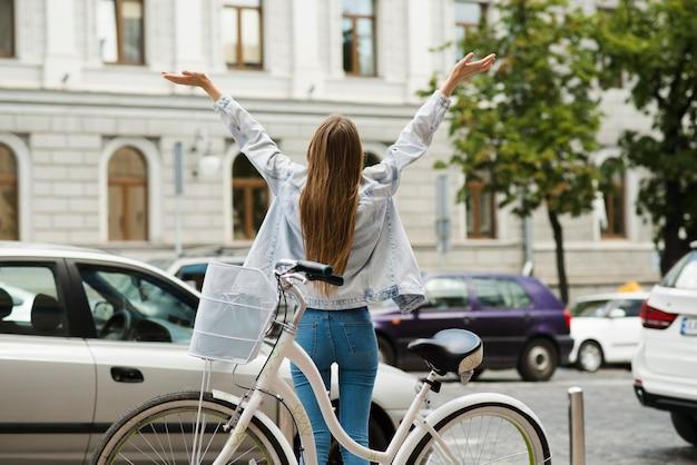Hintere ansicht einer glücklichen frau mit fahrrad