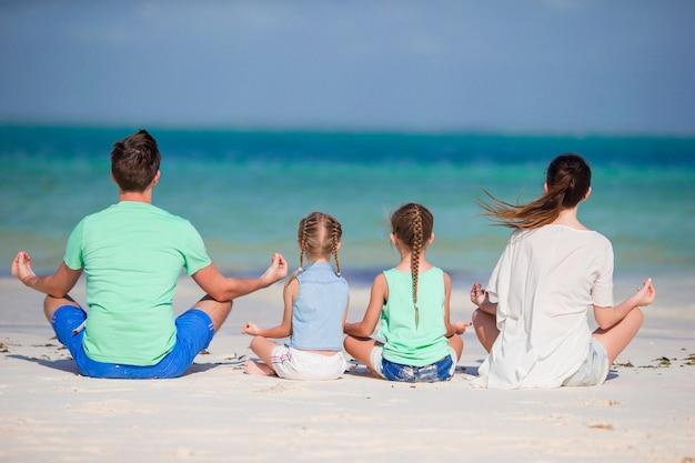 Hintere ansicht einer jungen familie auf tropischem strand